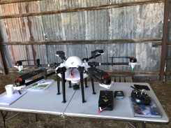 The drone retrofitted for herbicide application, with a 10L tank and spray nozzle at the end of each of the six arms.